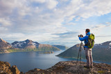 landscape photographer working with tripod and dslr camera in beautiful wild nature, standing with backpack on top of mountain - 164646144