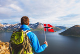 travel to Norway, hiker traveler with backpack holding norwegian flag and looking at beautiful fjord landscape - 164646168