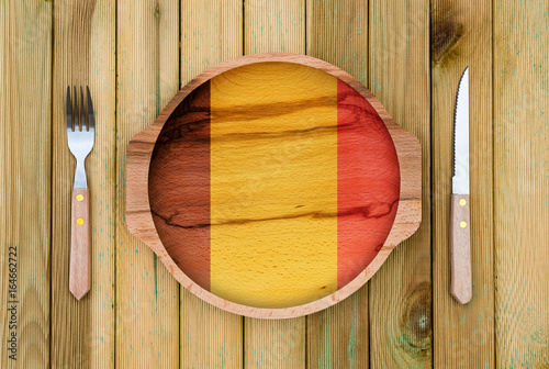 Concept of Belgium cuisine. Wooden plate with a Belgium flag, fork and knife on a wooden background