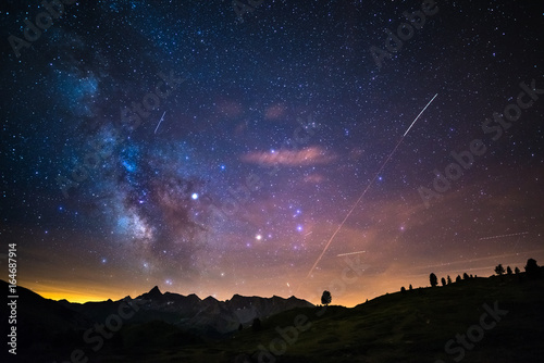 The colorful glowing core of the Milky Way and the starry sky captured at high altitude in summertime on the Italian Alps, Torino Province. Airplane traffic in the sky.