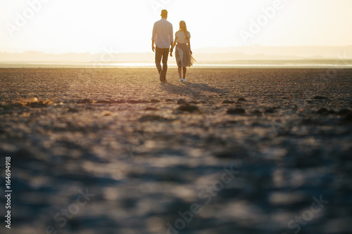 Couple in love walking on the beach and looking at each other