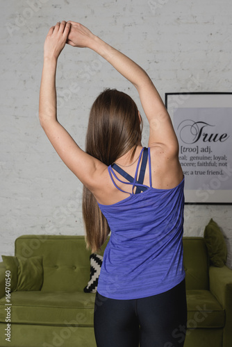 Beautiful young woman doing exercises at home. Portrait of attractive female relaxing at home in living room after yoga or pilates exercise