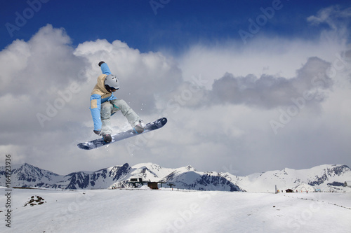 Flying snowboarder on mountains Poster