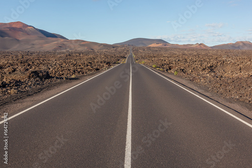 Poster Canarische Eilanden Picturesque road through volcanic terrain in the Timanfaya national park on Lanzarote island, Canary Islands, Spain
