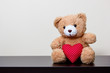 Quadro bear doll and red heart on wooden table