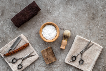 Preparing for men shaving. Shaving brush, razor, foam, sciccors on grey stone table background top view copyspace