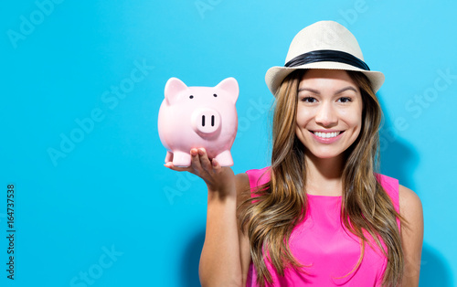 Young woman with a piggy bank on a blue background - 164737538