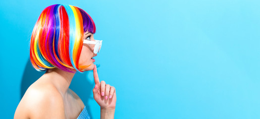 Beautiful woman in a colorful wig on a blue background © Tierney