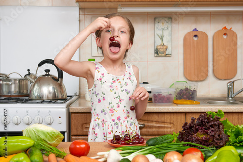 child girl eat cherries, fruits and vegetables in home kitchen interior, healthy food concept