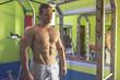 Bodybuilder posing in gym. Perfect muscular male body