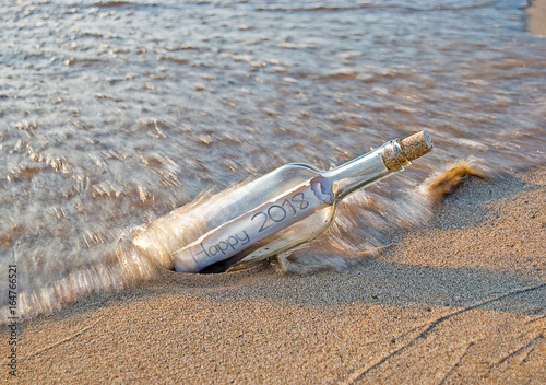Poster New Year 2018 message in a bottle on the beach with splashing wave