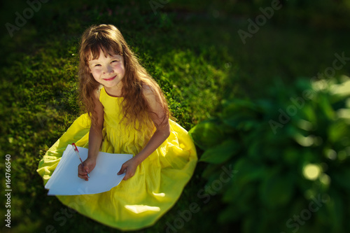 Plakat A girl in a yellow dress sits on the grass and draws