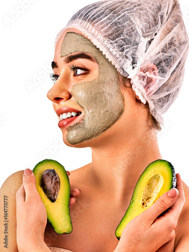 Avocado clay face mask. Woman in medical hat holding half of green fruit with stones isolated background. Facial beautiful procedure concept. Cosmetic mask against black dots. Elite spa salon.