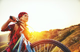 Woman tourist on a bicycle at top of mountain at sunset outdoors during  hike in summer - 164775398