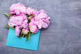 Bouquet of peony flowers with envelope on grey wooden table