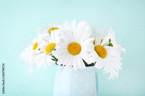 Bouquet of chamomile flowers in jug on mint background