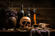 Still Life Skull , Bone ,Wine Bottles , Candle Light , on Old Wood Table Background - Halloween or Esoteric Concept