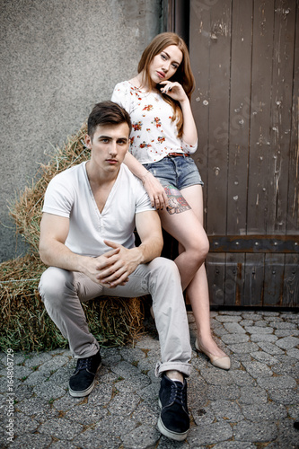 Portrait of young modern couple in love, posing outdoors in city street