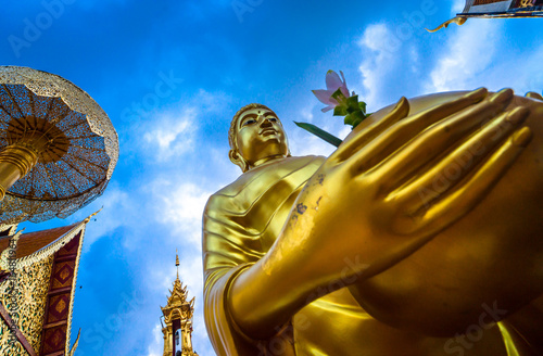 Golden buddha statue with blue sky background , At Wat Phra That Doi Suthep temple is tourist attraction of Chiang Mai, Thailand. Focus at face of buddha statue.