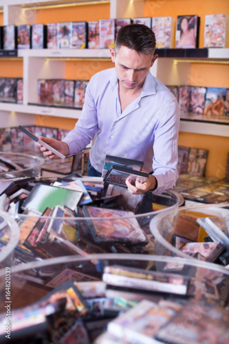 Poster Man buying erotic films in sex shop