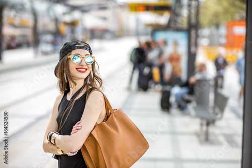Lifestyle portrait of a stylish woman in black dress and hat standing with bag o