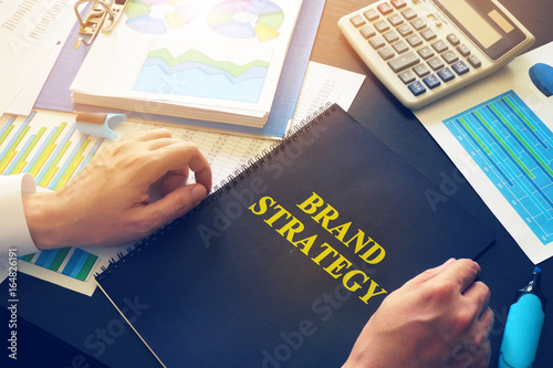 Businessman taking document with name Brand Strategy.