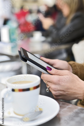 woman using a tablet in the terrace of a cafe