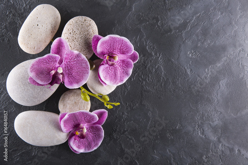 Lilac orchids and white stones lie on black marble. Spa.