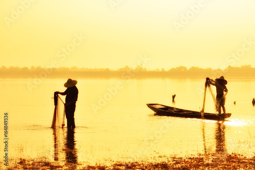 Fishing man in silhouette on gold sunset background.