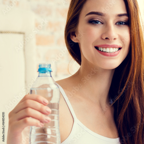 woman with bottle of water, at home