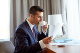 businessman with papers drinking coffee at hotel - 164859198
