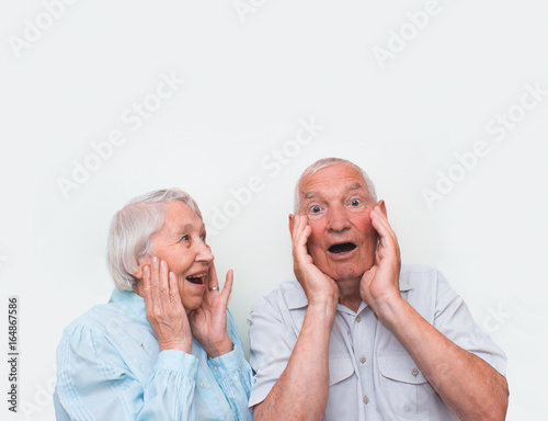 The elderly couple surprised by raising both hands Poster