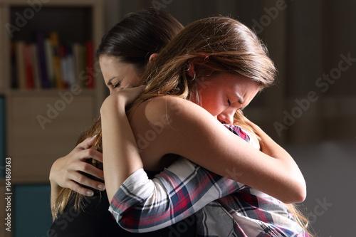 Leinwandbild Motiv Two sad teens embracing at bedroom