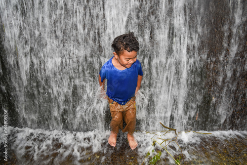 Boy under waterfall Poster