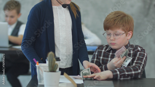 Little businessman holding money and giving salary in office