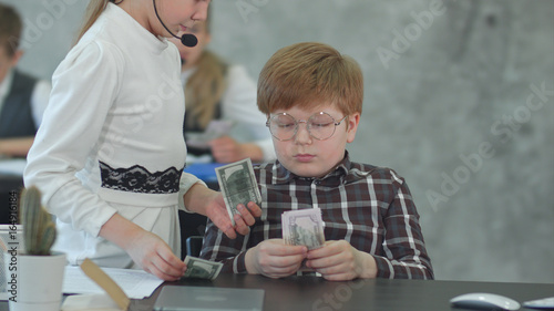 Young pensive boy counting money and giving salary