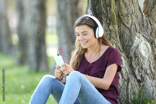 Teen listening music on line in a park - 164926395