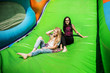 Leinwanddruck Bild - Gorgeous girls having fun on a slide on a sunny day.