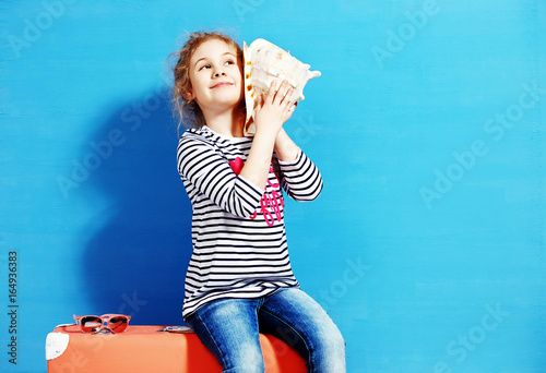 Portrait of blonde child girl listen a seashell at the blue wall
