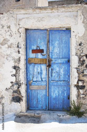 Foto Murales Bright blue old weathered door on the island of Santorini, Greece, Europe.