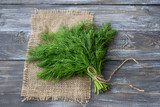 Bunch of fresh dill on a wooden surface with free space. Rustic style, selective focus - 164937911