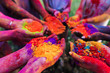 Quadro close-up partial view of young people holding colorful powder in hands at holi festival