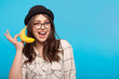 Smiling woman posing with banana on blue