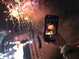 Hand holding an iphone recording foreworks at the end of a concert.