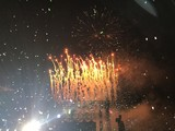 Fireworks outside at a concert in the summer.
