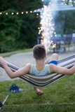 Teen boy relaxes in hammock while watching fireworks.
