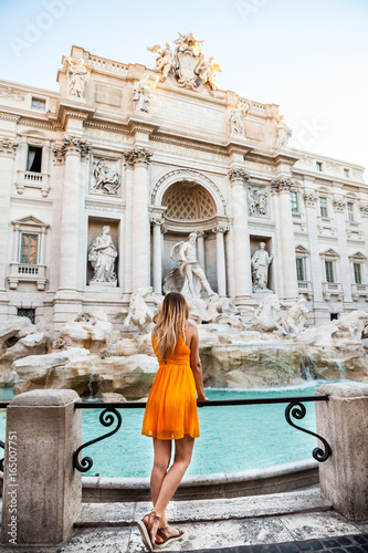 Girl in yellow dress in front of Trevi Fountain, Rome, Italy. Young pretty girl with blonde hair in a yellow dress. Photo shooting in Rome, Italy