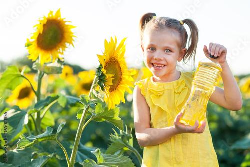 Little beautiful girl near a sunflower with a bottle of sunflower oil