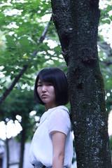 木にもたれ掛かる女性