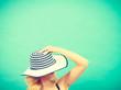 Woman hiding face behind sun hat